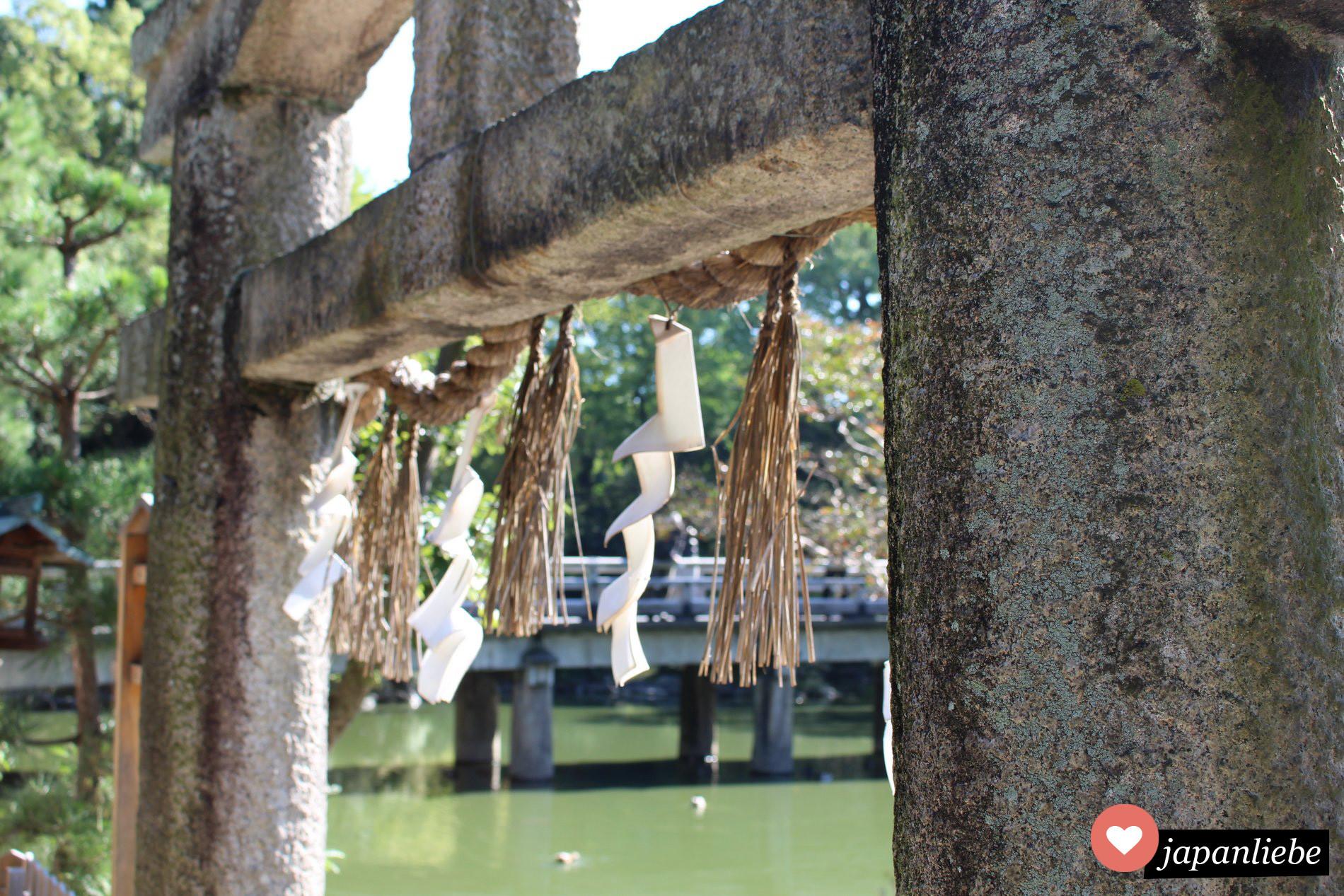 Stein-torii mit shide  Zickzack-Papier am Itsukushima Schrein in Kyōto.
