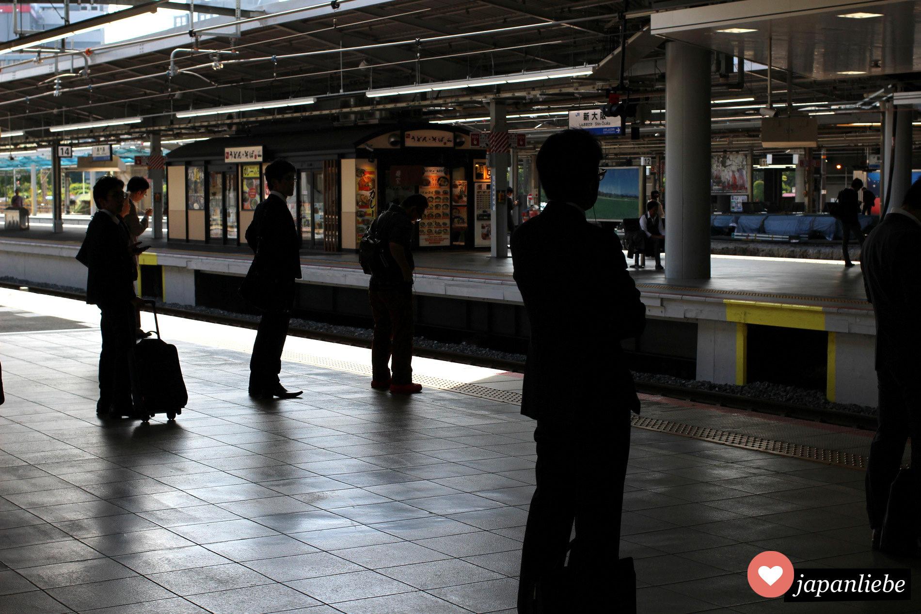 Japanische Pendler und Reisende am Bahnhof Shin-Osaka