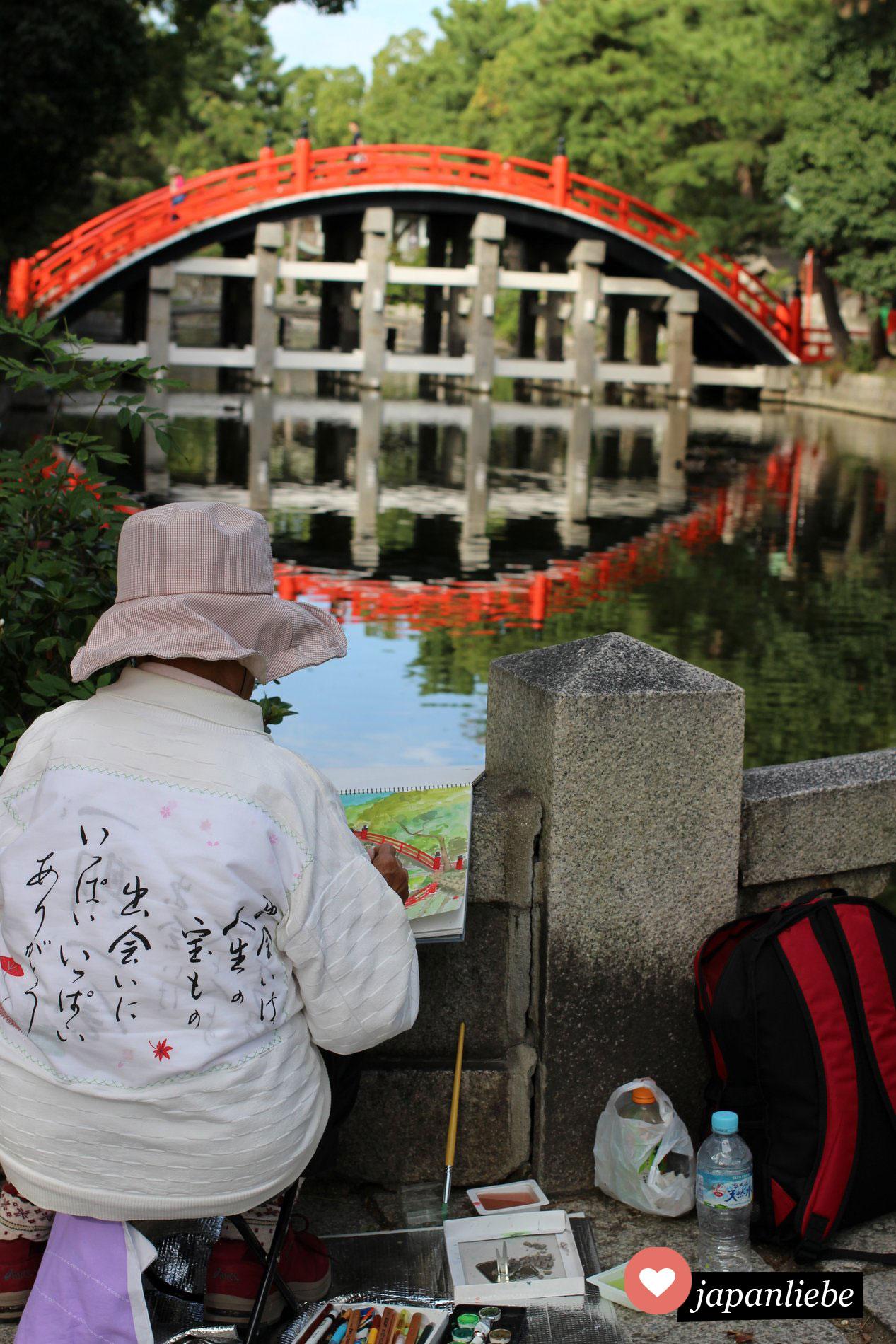 Eine Malerin zeichnet die Trommelbrücke des Sumiyoshi Taisha Schreins in Osaka, Japan