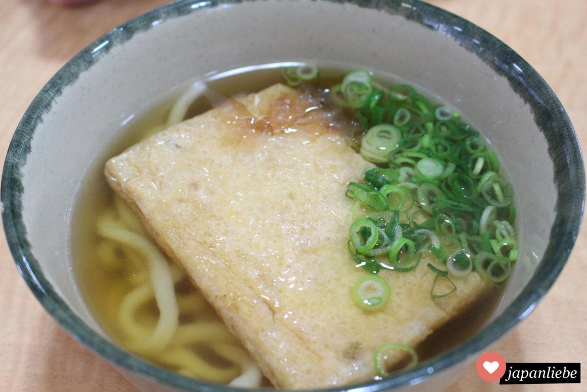 Kitsune Udon Nudelsuppe mit einer großen Scheibe Tofu.