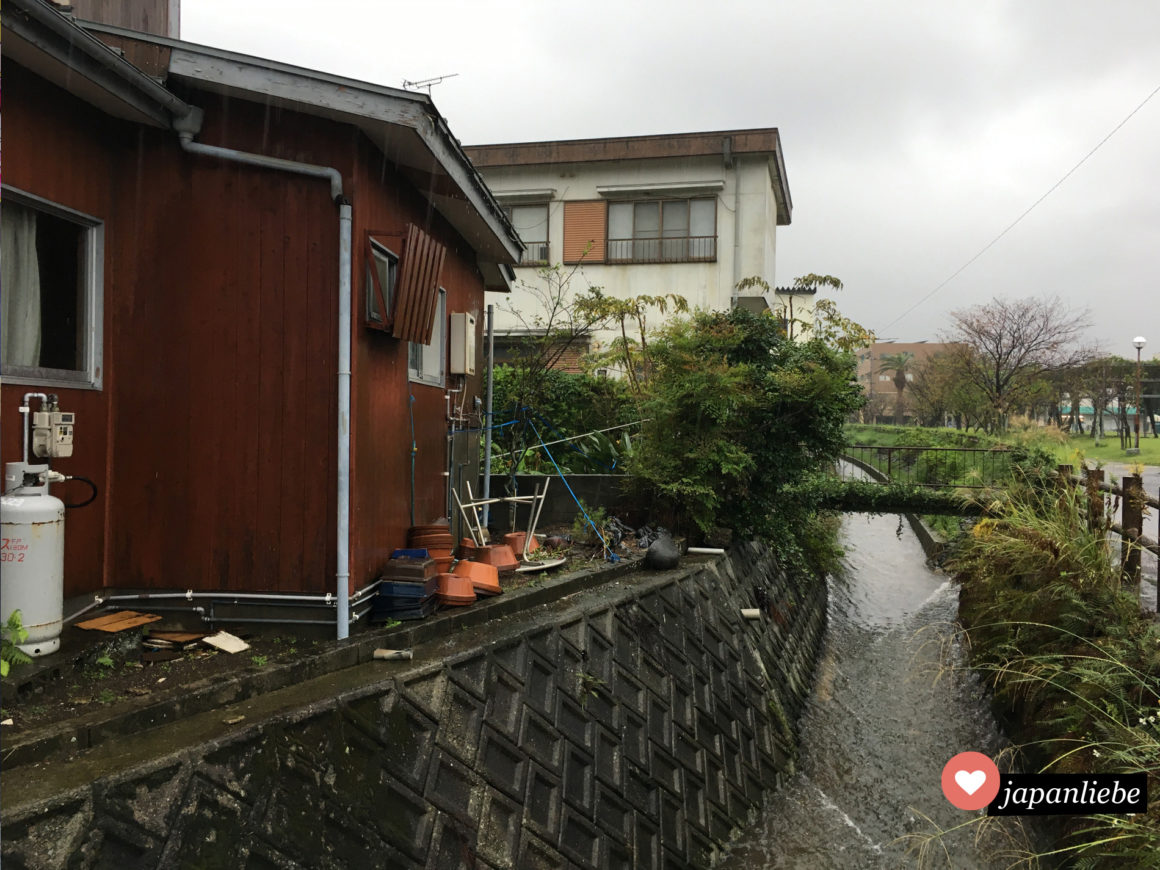 Ein Wohnhaus neben einem kleinen Kanal in Ibusuki.