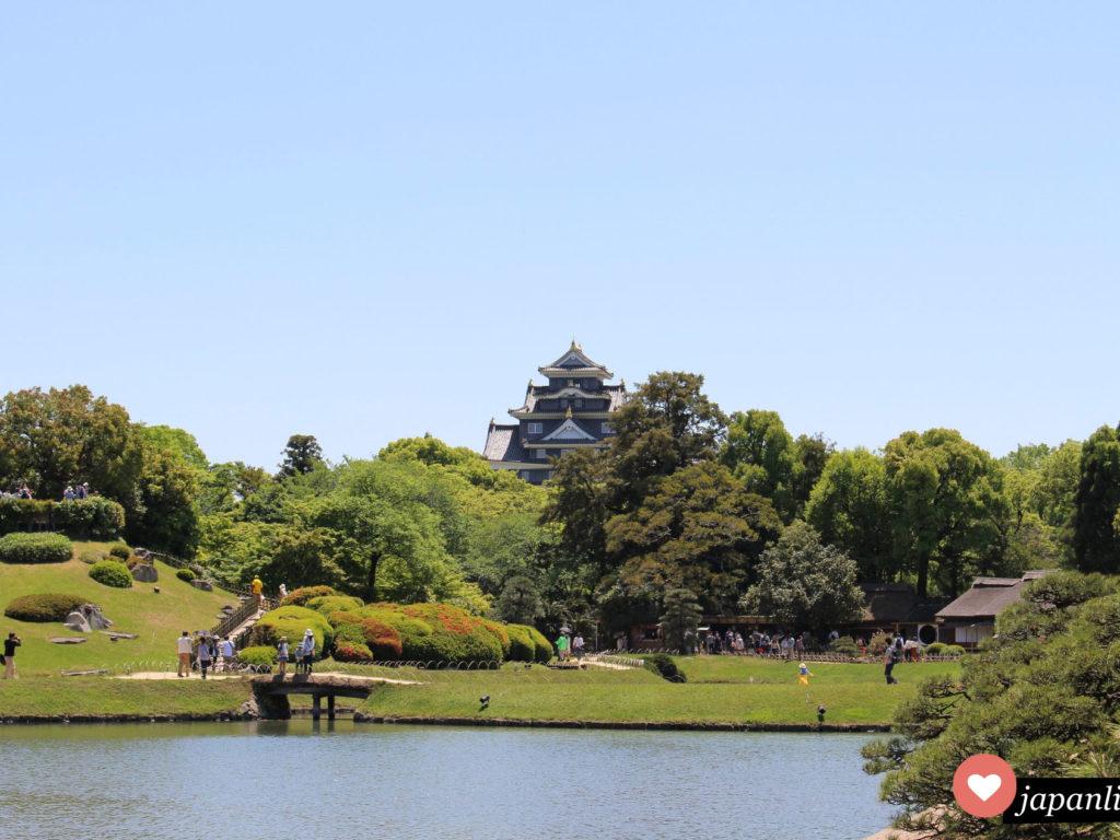 Der Korakuen Garten In Okayama mit schwarzer Burg im Hintergrund