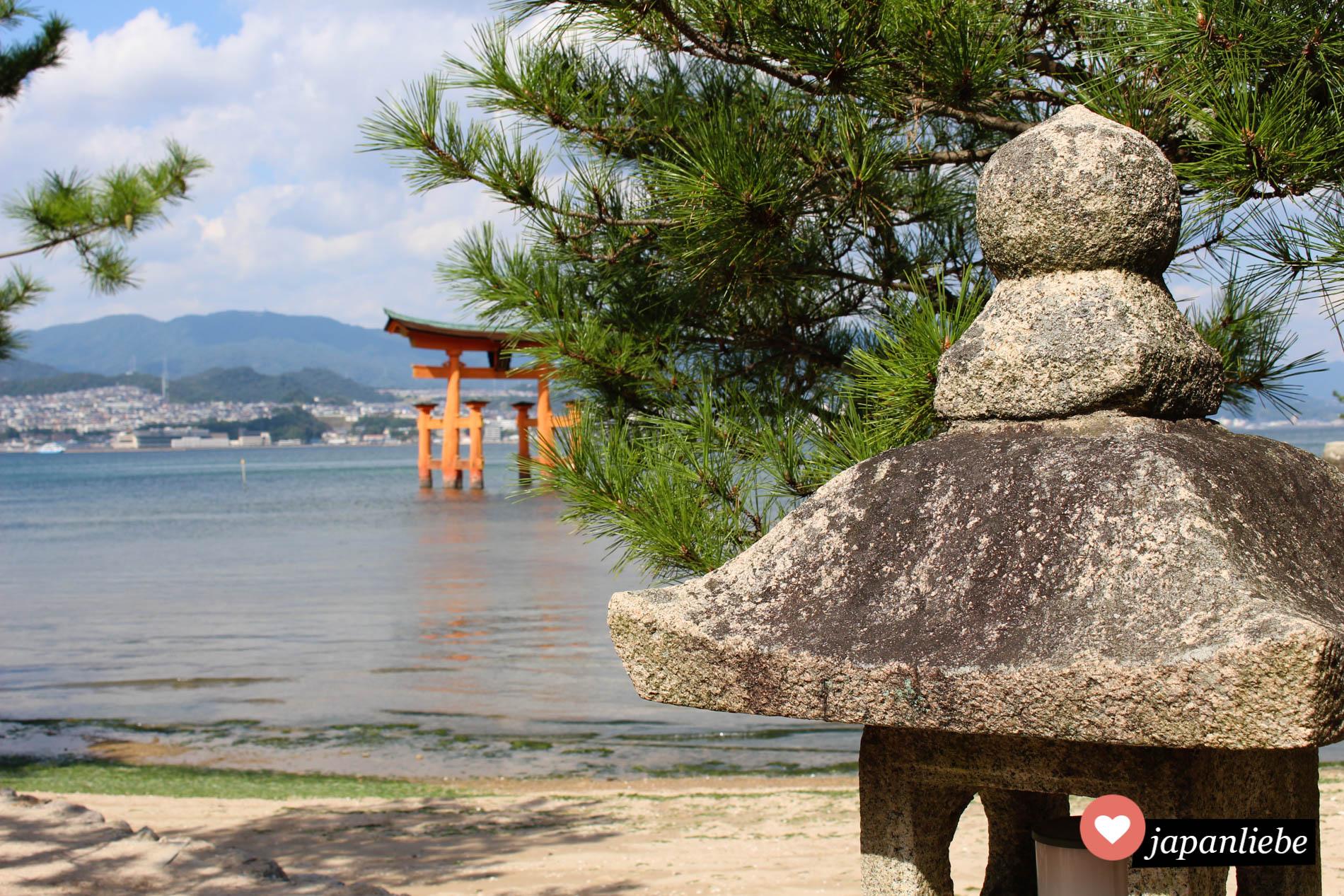 japans berühmtestes torii auf Miyajima vom Strand aus fotografiert, inklusive Steinlaterne im Bild.