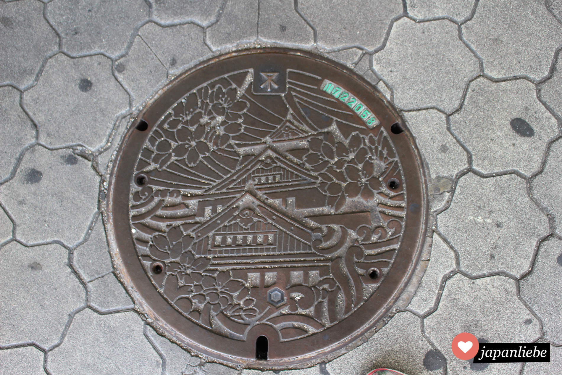 Eine Reihe an Kanaldeckeln in Osaka zeigen die Burg der Stadt mit Kirschblüten.
