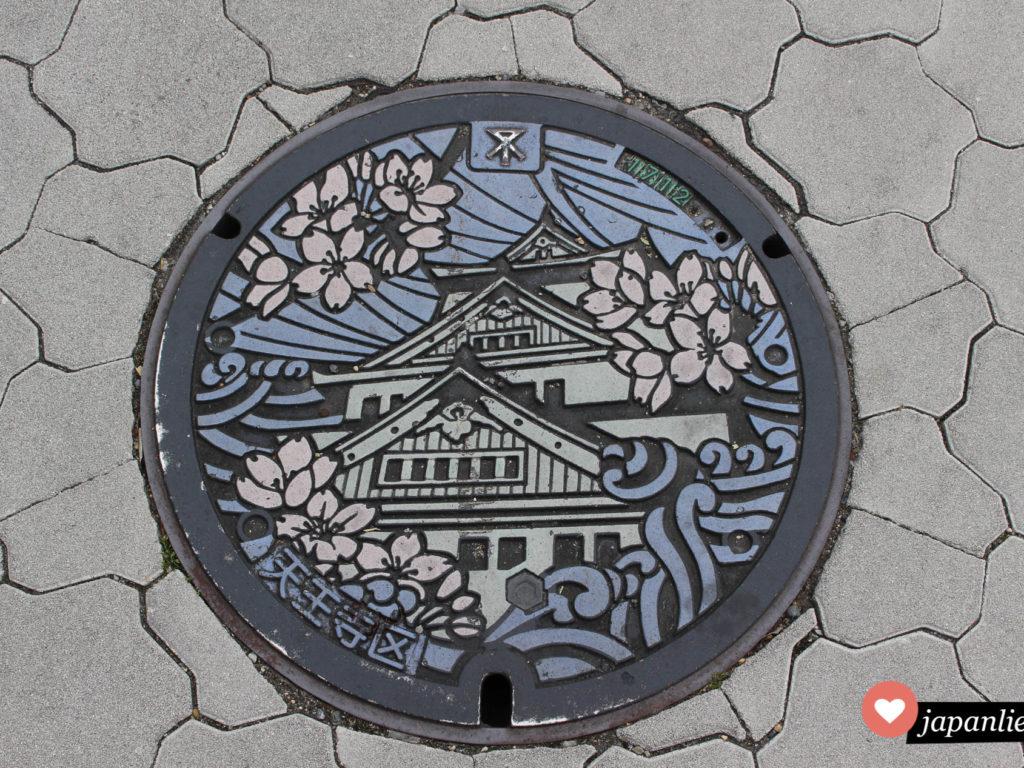 Ein besonders hübscher Kanaldeckel in Osaka zeigt Burg und Kirschblüten in Farbe.