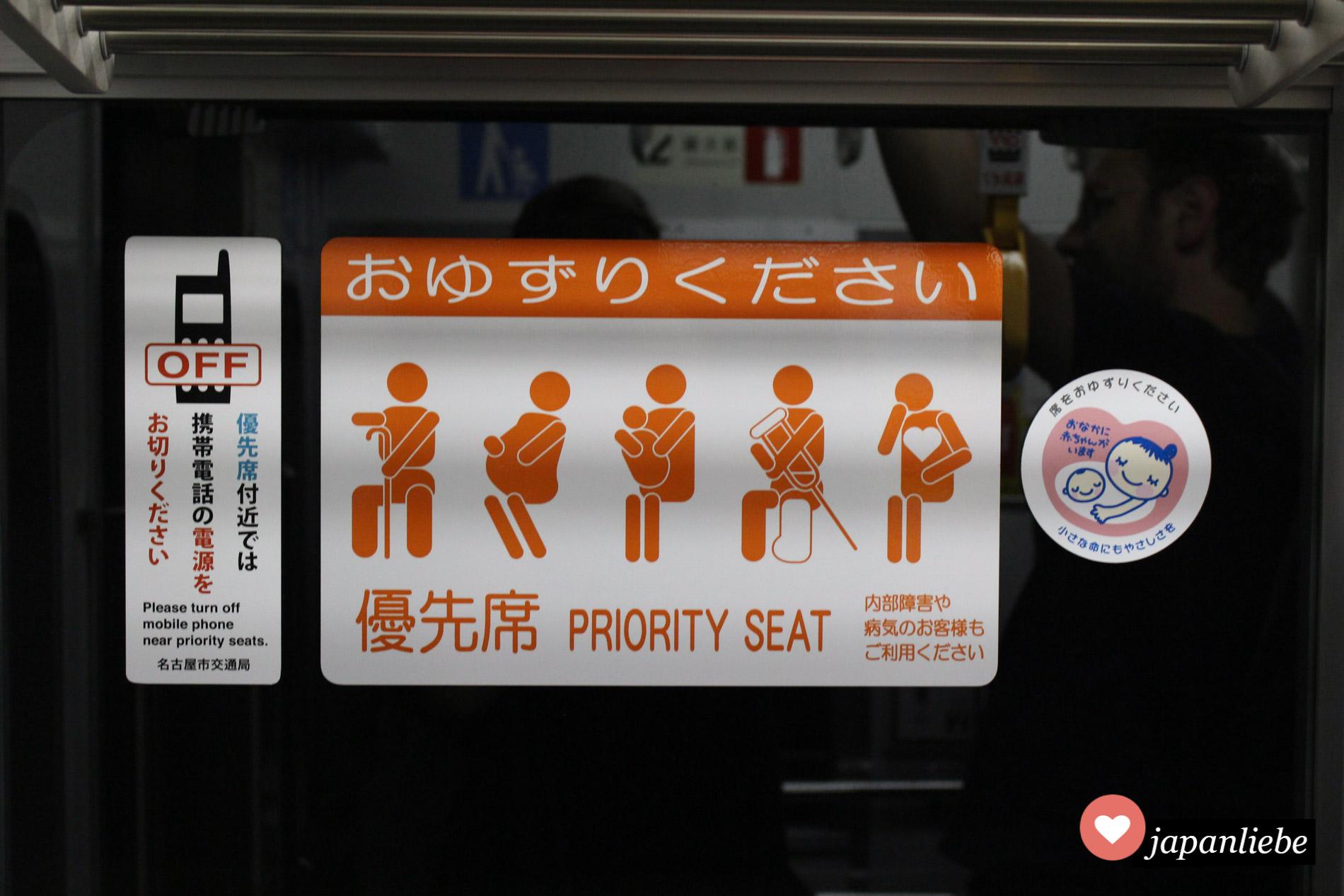 """Im Bereich der Priority Seats sollen Handys möglichst ausgeschalten werden. Rechts im Bild das Zeichen für Schwangere: """"Ich habe ein Baby im Bauch."""""""