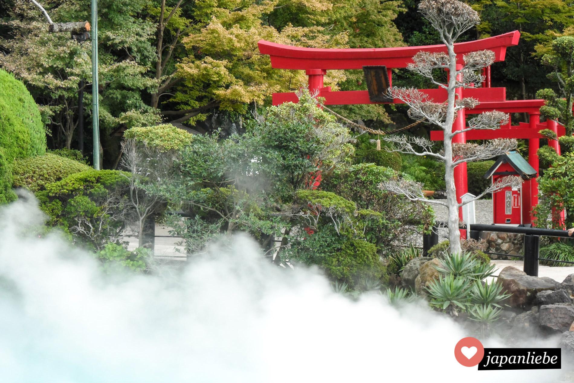 Ein rotes torii vor den Rauchschwaden in der Meerhölle in Beppu.