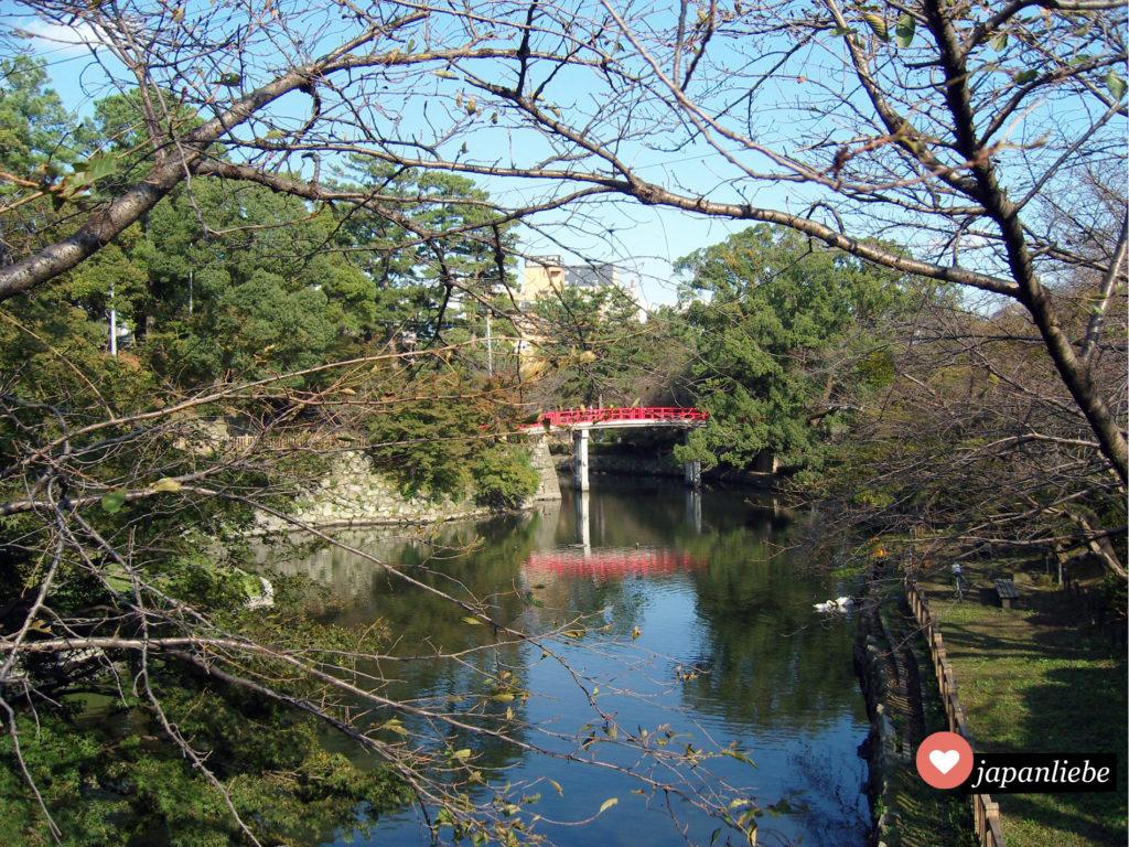 Ein sehr typisch japanischer Anblick: eine rote Brücke spannt sich über den Fluss im Schlosspark von Okazaki.