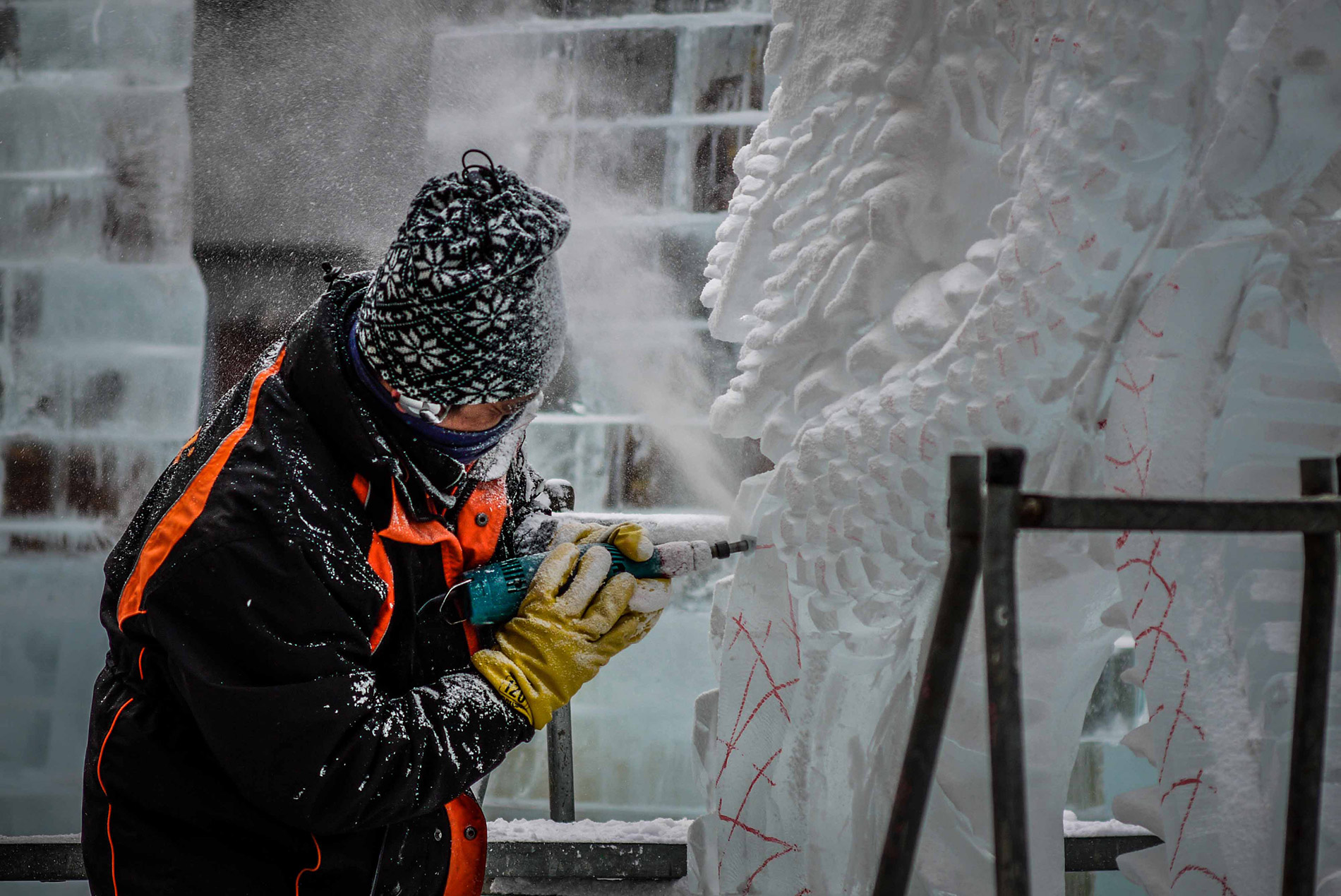 Ein Schneekünstler bearbeitet eine Skulptur beim Sapporo Snow Festival.