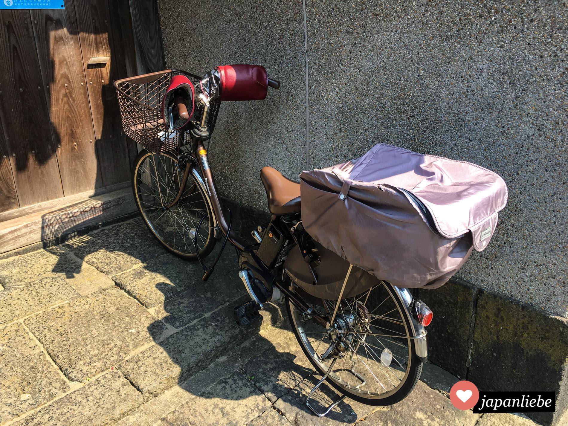 Ein Fahrrad in Japan mit festmontiertem Sonnenschutz an den Griffen.