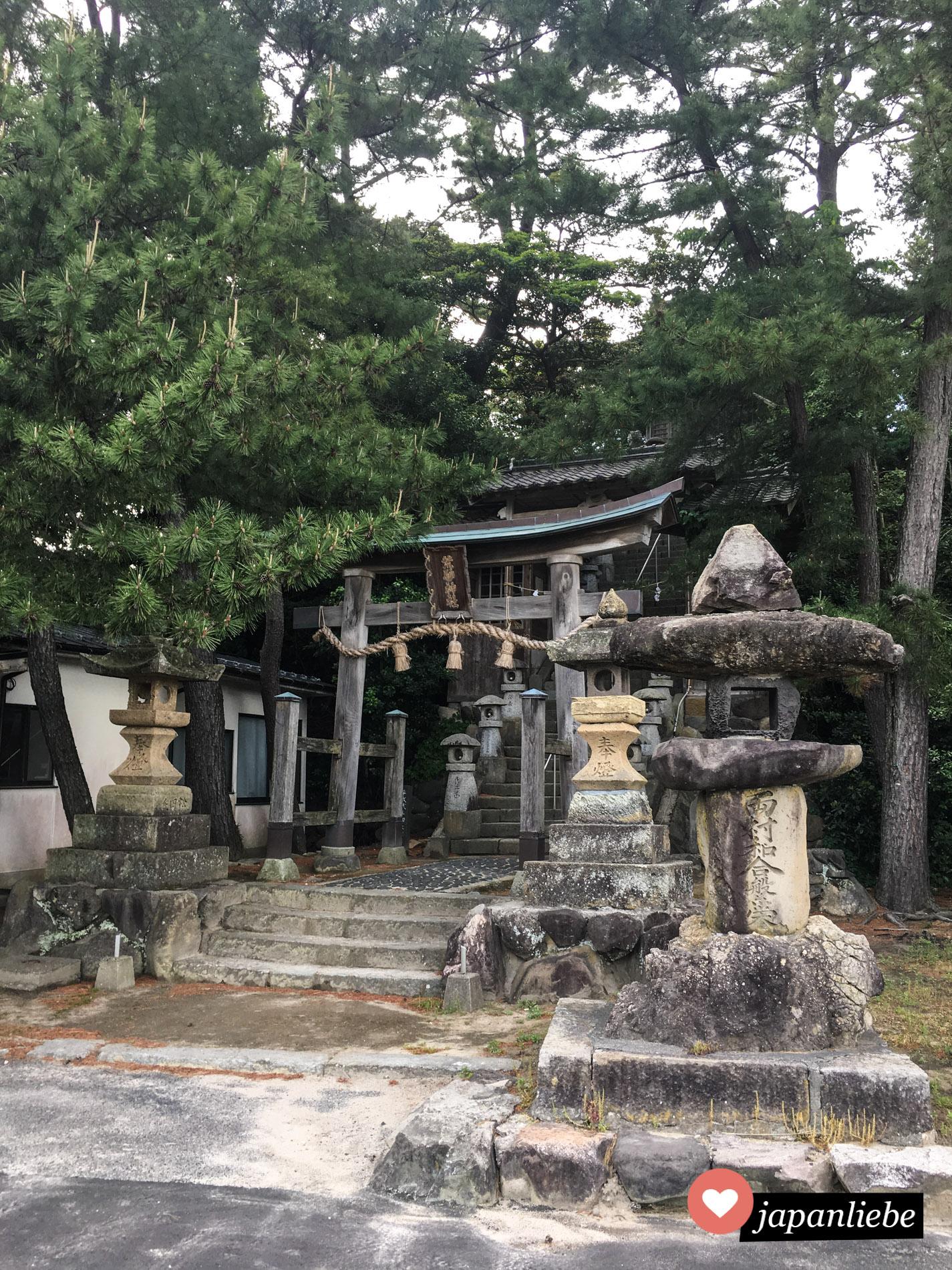 Ein Stein-Torii und Laternen kennzeichnen den Eingang zum Arasuna Schrein in Iwami.