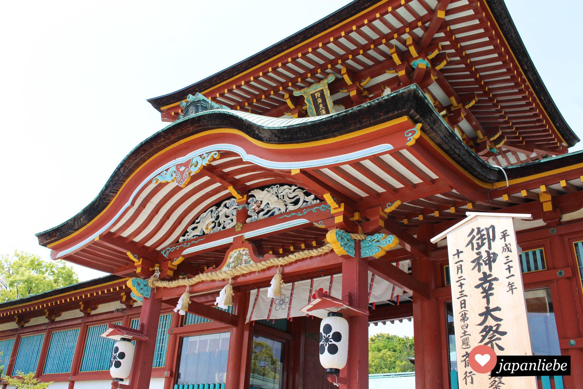 Das Eingangstor ist leuchtend rot und prächtig mit Schnitzereien geschmückt.