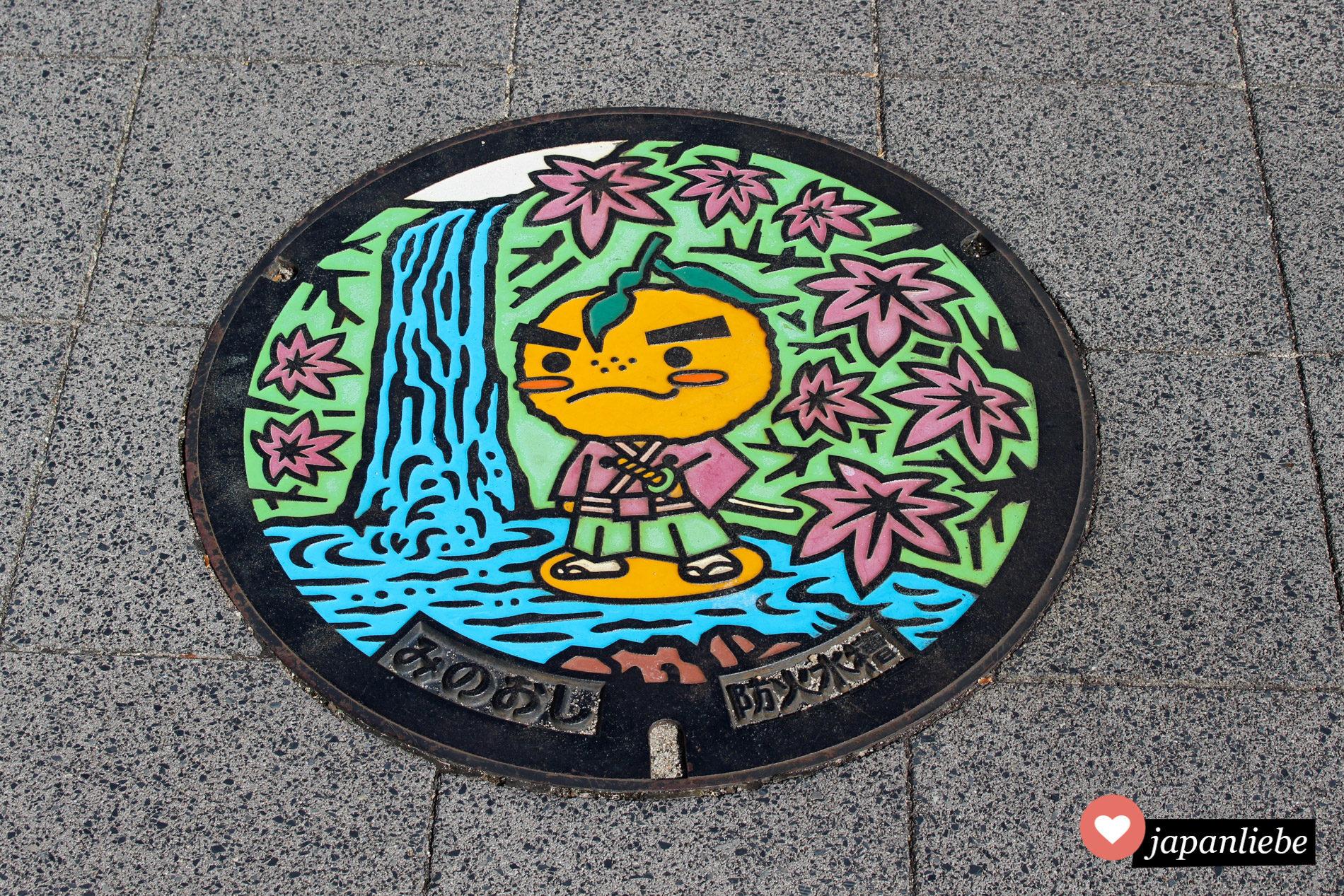 Einer der Kanaldeckel in Minoo zeigt das Stadtmaskottchen: Takinomichi Yuzuru.
