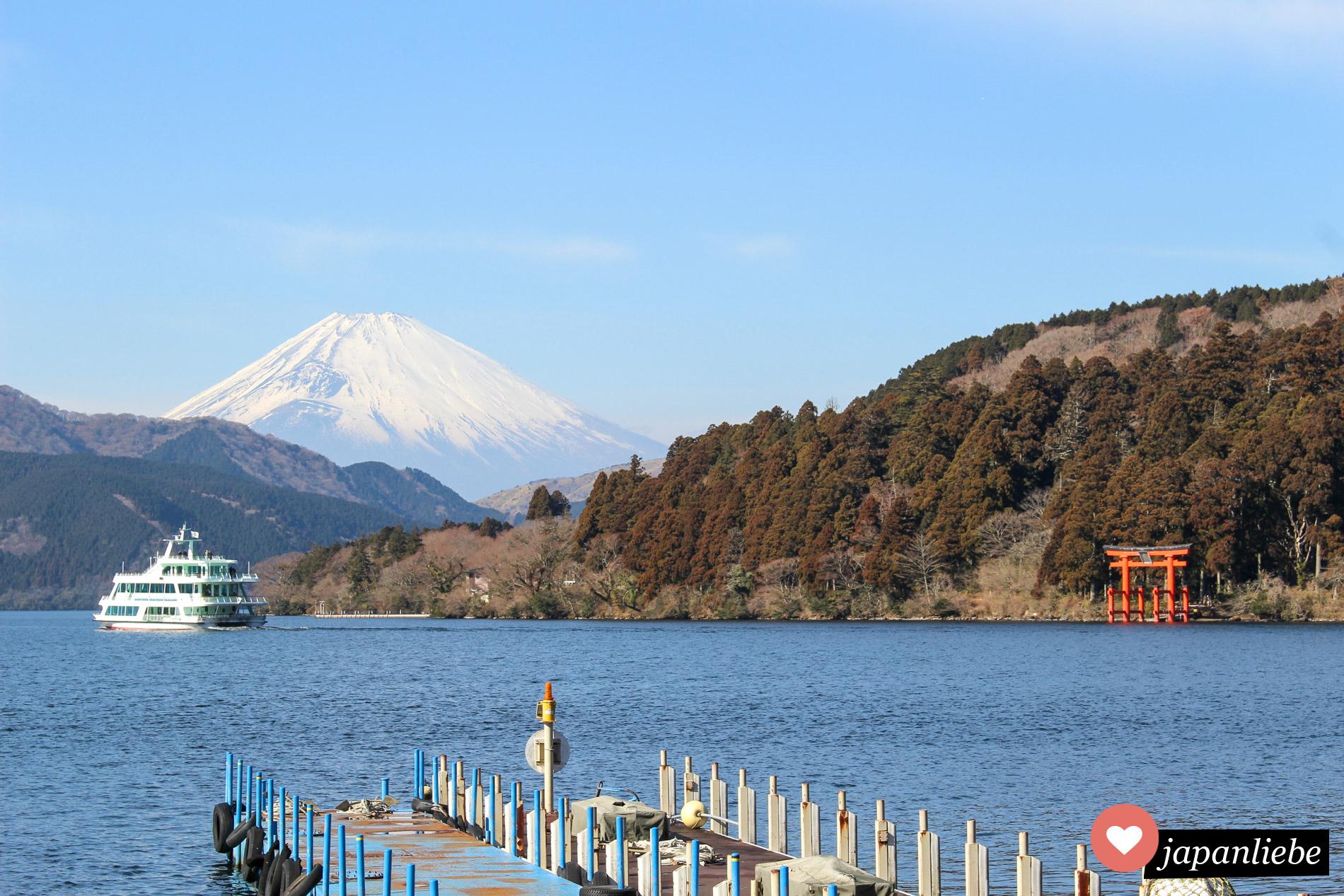 Ikonisches Postkartenmotiv: das rote torii des Hakone Schreins am Ashi-See mit dem Fuji im Hintergrund.