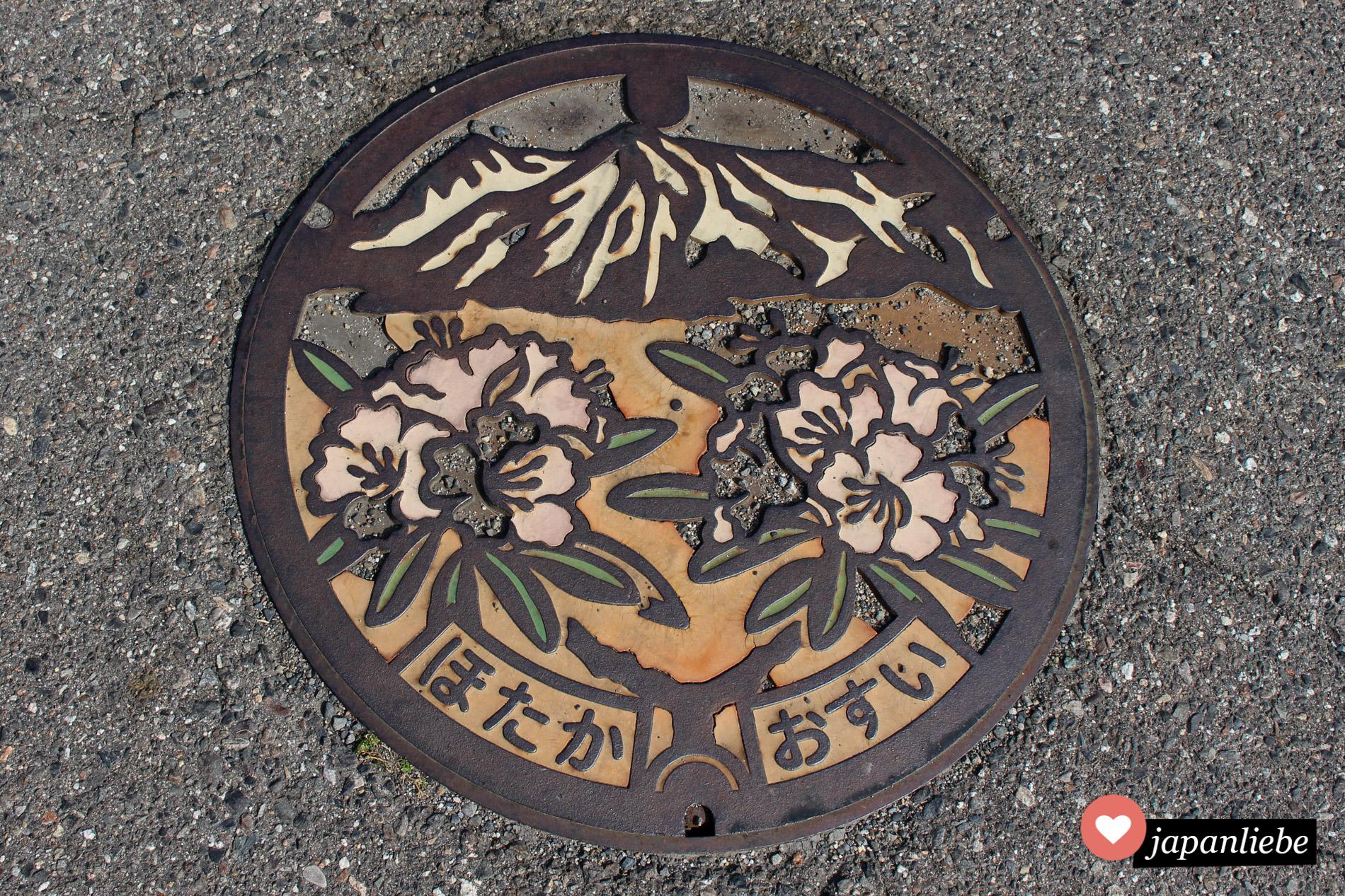 Der Kanaldeckel der Stadt Hotaka zeigt Rhododendron und die japanischen Alpen.
