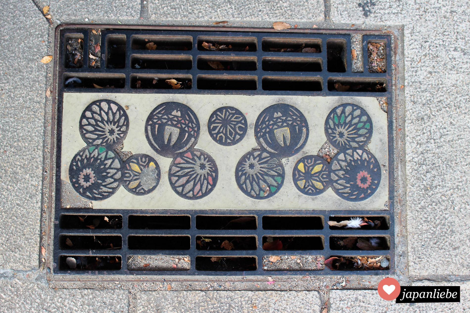 temari-Bälle zieren ein Gitter auf einem Gehsteig der Stadt Matsumoto.