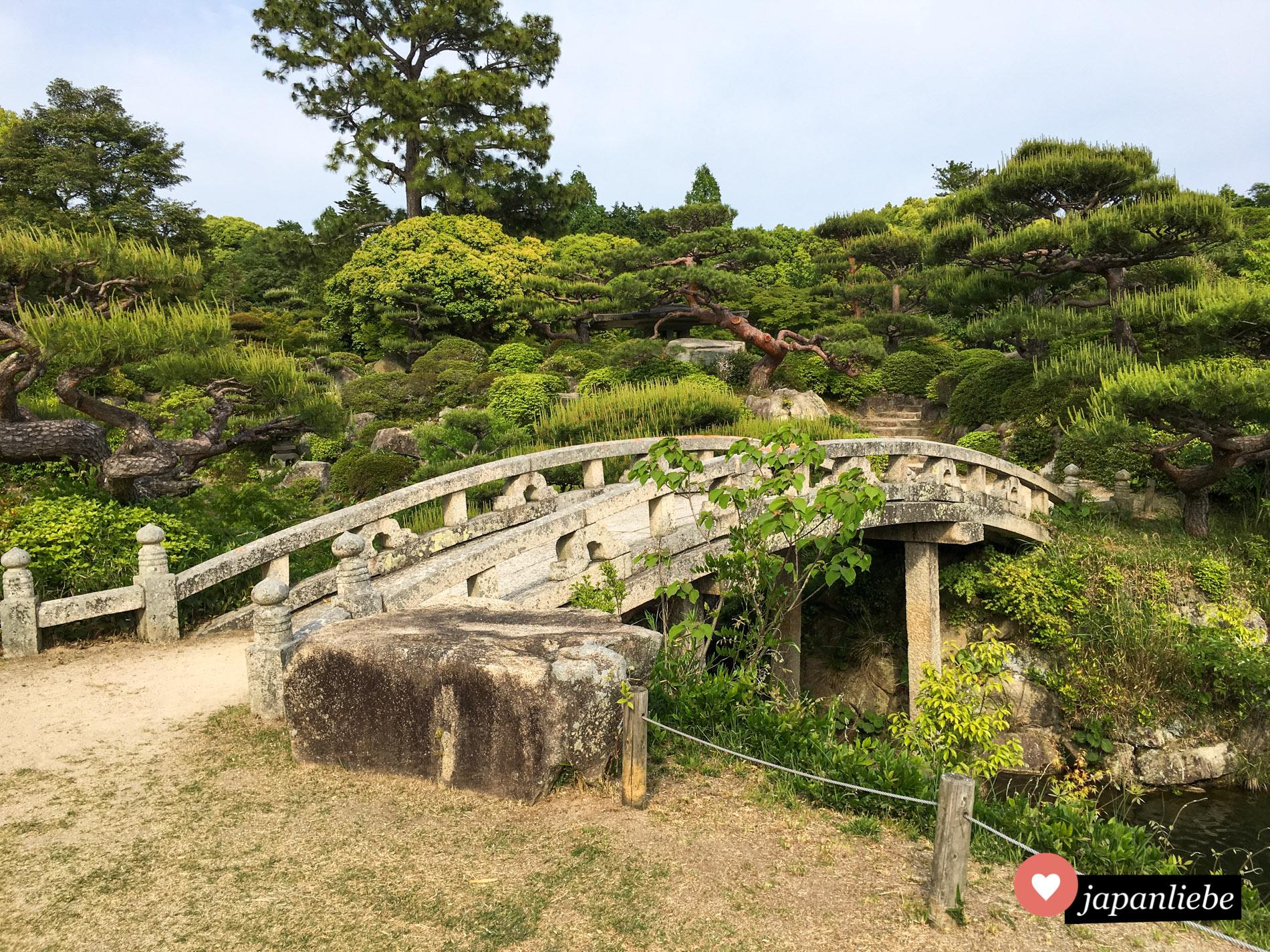 Eine Bogenbrücke überspannt einen der Teiche im Mōri Garten.