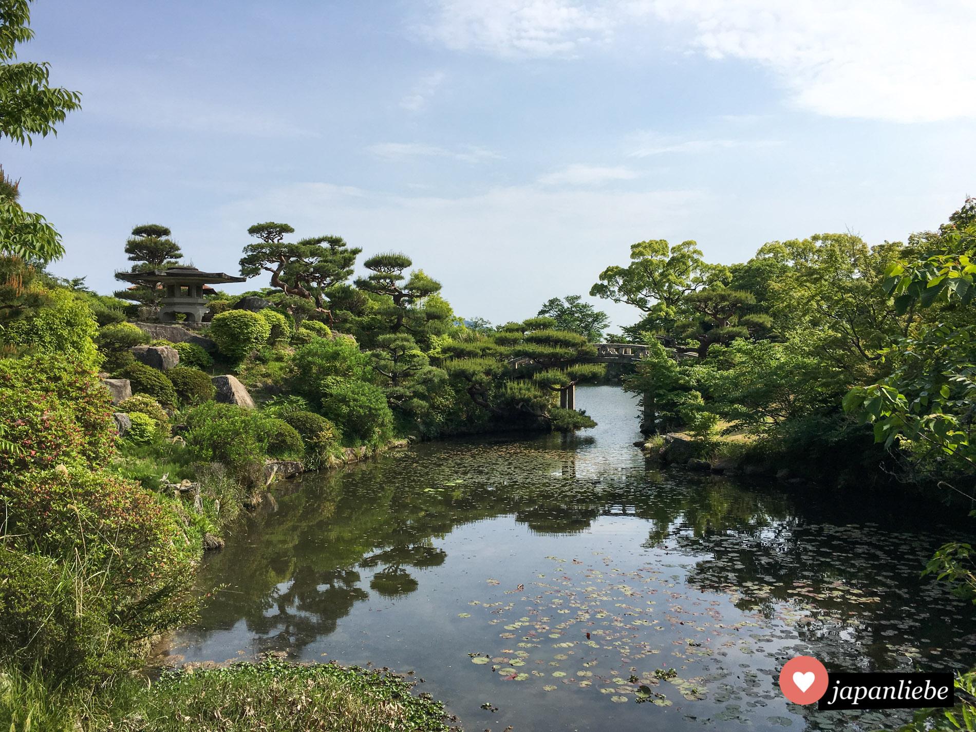 Blick auf die Wahrzeichen des Mōri Garten in Hōfu: Brücke und Steinlaterne.