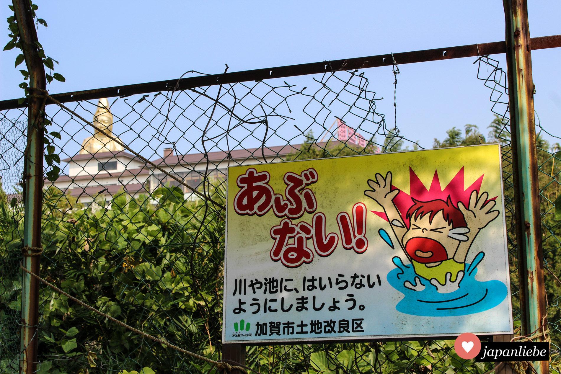 Ein Schild in Kaga-Onsen warnt davor, dass Schwimmen an dieser Stelle zu gefährlich ist. Im Hintergrund wacht eine riesige, goldene Buddhastatue darüber, ob dieses Verbot auch eingehalten wird.