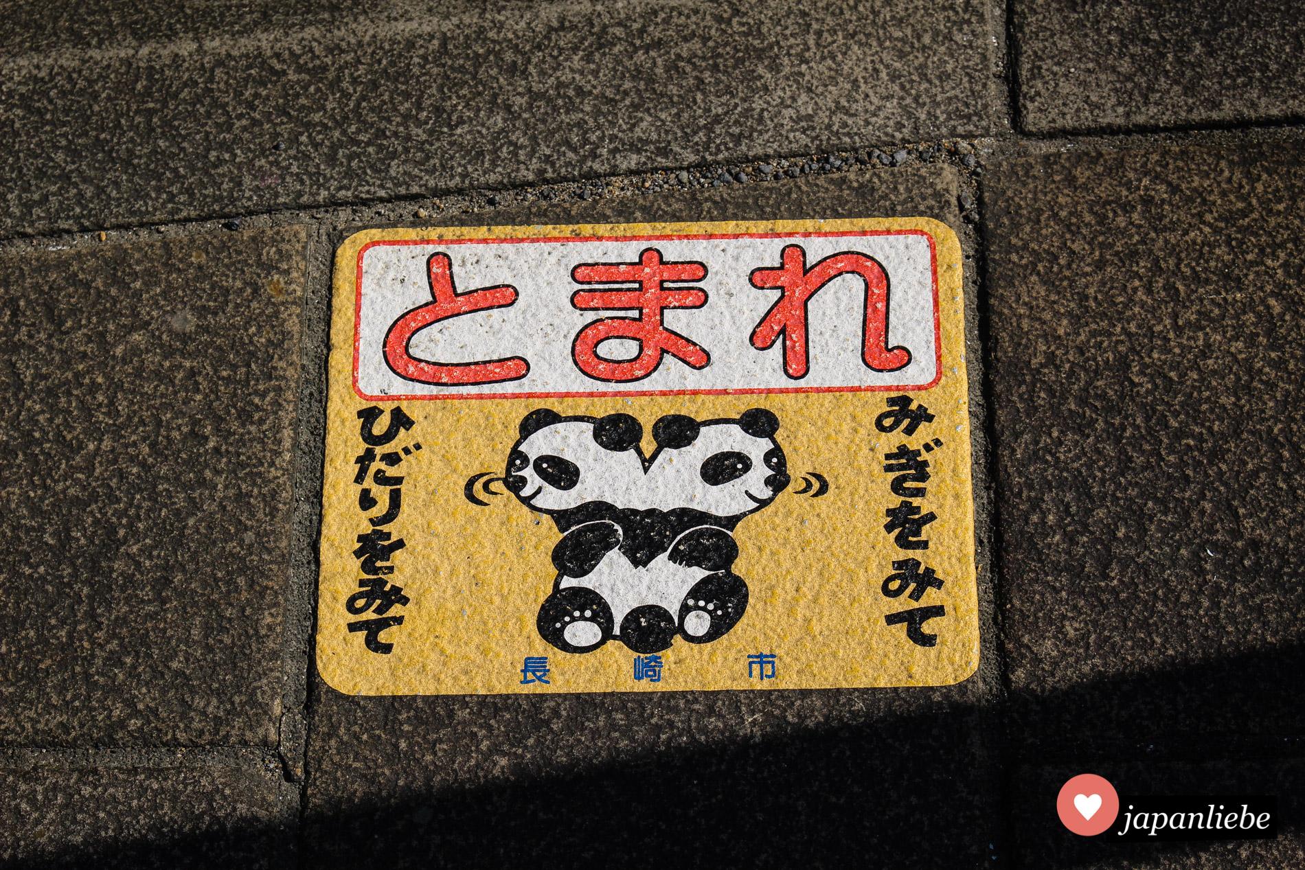 Im Straßenverkehr rund um Nagasakis Chinatown weißen Pandabären dazu an, an gefährlichen Stellen stehenzubleiben.