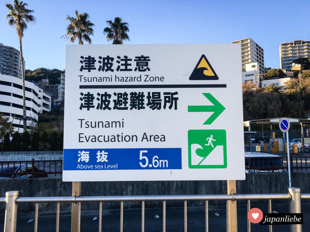 Ein Schild am Strand von Atami zeigt an, wohin man sich im Fall eines Tsunamis begeben sollte.