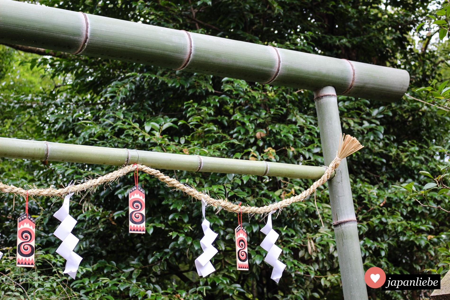Einfache shide Zickzack-Streifen an einem Bambus-torii des Fushimi Kandakara Schreins.