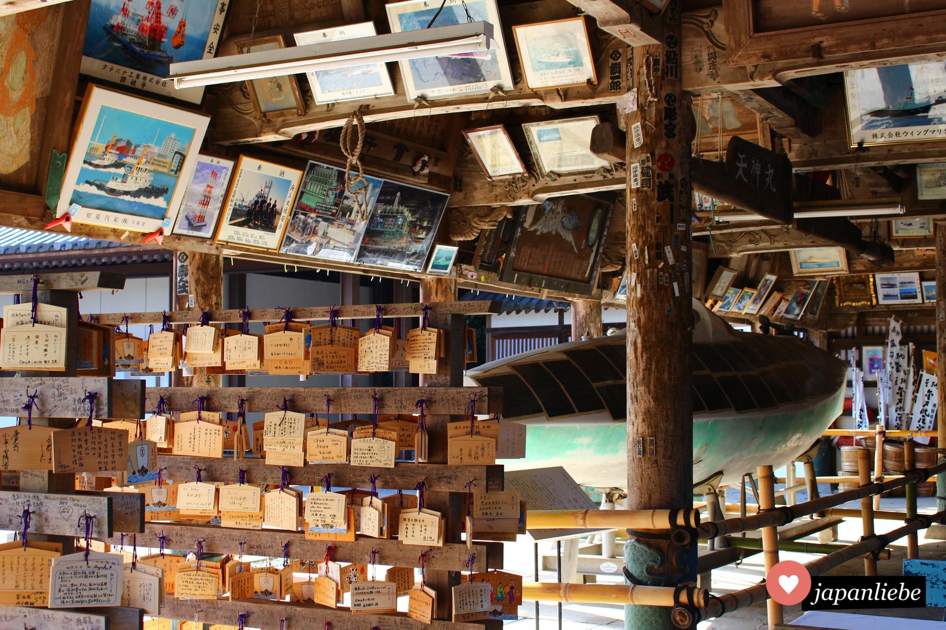 In der Votivhalle am Kotohira-gū finden sich diverse Opfergaben wie ema-Täfelchen und auch gerahmte Bilder. Dazwischen lassen sich einige Pilger-Namensaufkleber entdecken.