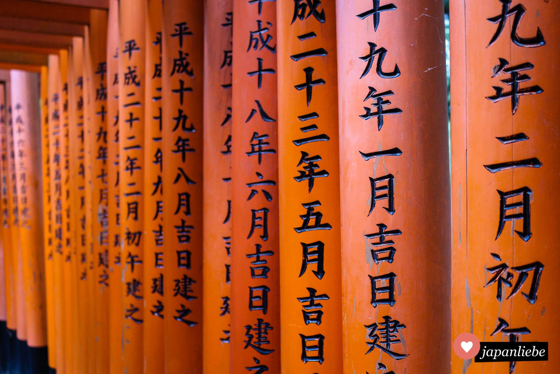 Die Schriftzeichen auf den vielen roten toren an Inari-Schreinen verraten, wer das jeweilige torii gespendet hat.