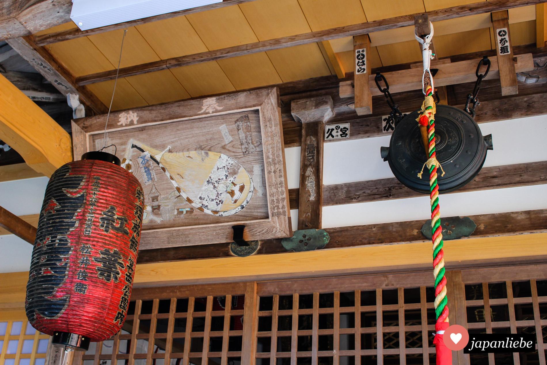An der Benten-dō Halle des Ryuan-ji Tempels im Minoo Park sind einige senjafuda Pilger-Namensaufkleber an ganz besonderen Stellen zu finden.