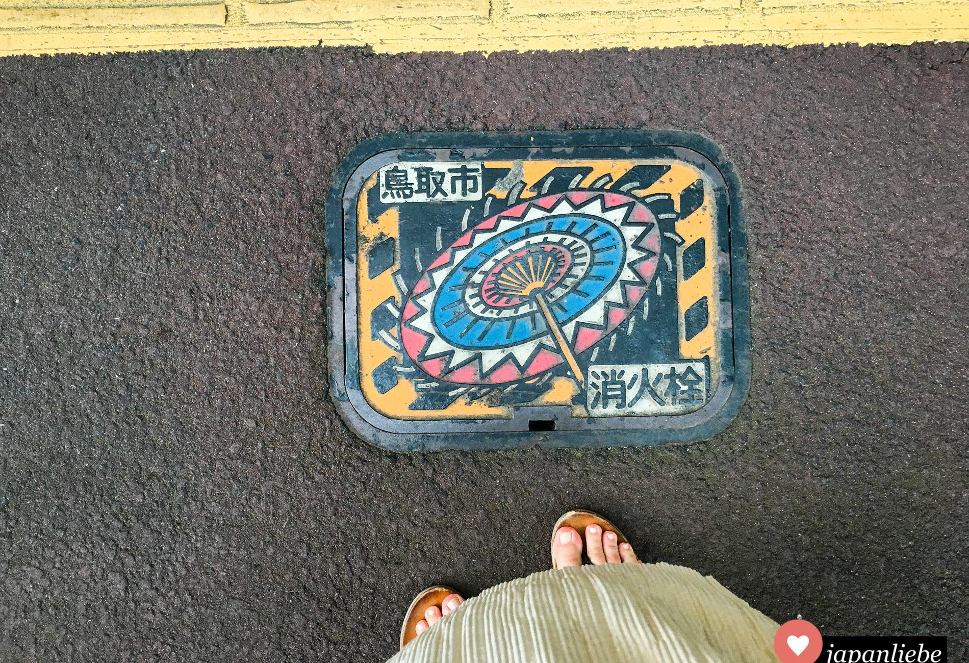 Ein Löschwasser-Kanaldeckel in der japanischen Stadt Tottori zeigt einen bunten Shanshan-Papierschirm.
