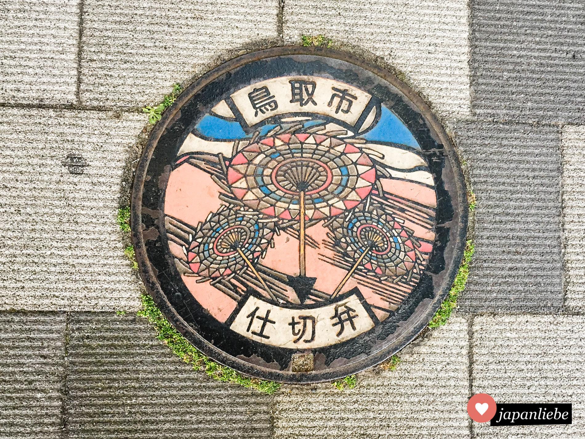 Ein Kanaldeckel zeigt gemeinsam die beiden großen Highlights von Tottori: Shanshan-Schirme und Sanddünen.