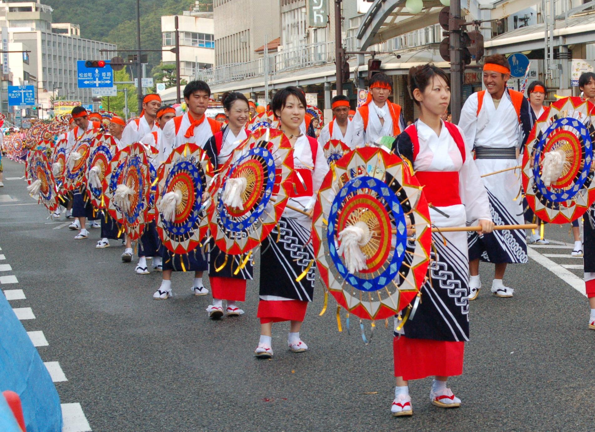 Laut, bunt, fröhlich – über 4.000 Teilnehmer tanzen beim Shanshan-Festival mit bunten Papierschirmen durch die Stadt Tottori. (Foto: Carampaima auf Wikimedia Commons https://commons.wikimedia.org/wiki/File:Kasa-odori_Parade.jpg Public Domain)