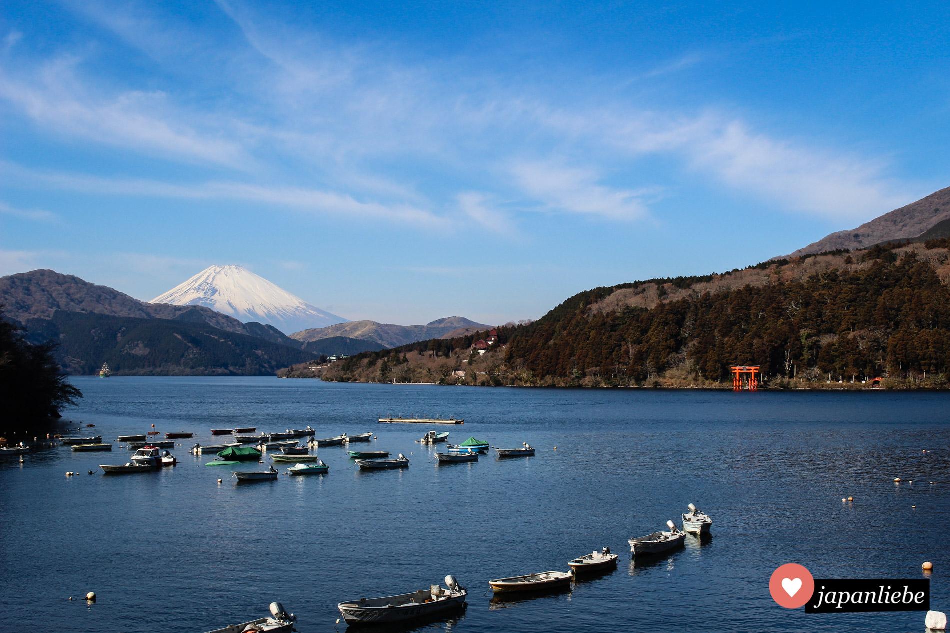 Idyllisch liegen Boote im Wasser des Ashi-Sees. Im Hintergrund ragt imposant der Fuji-san auf.