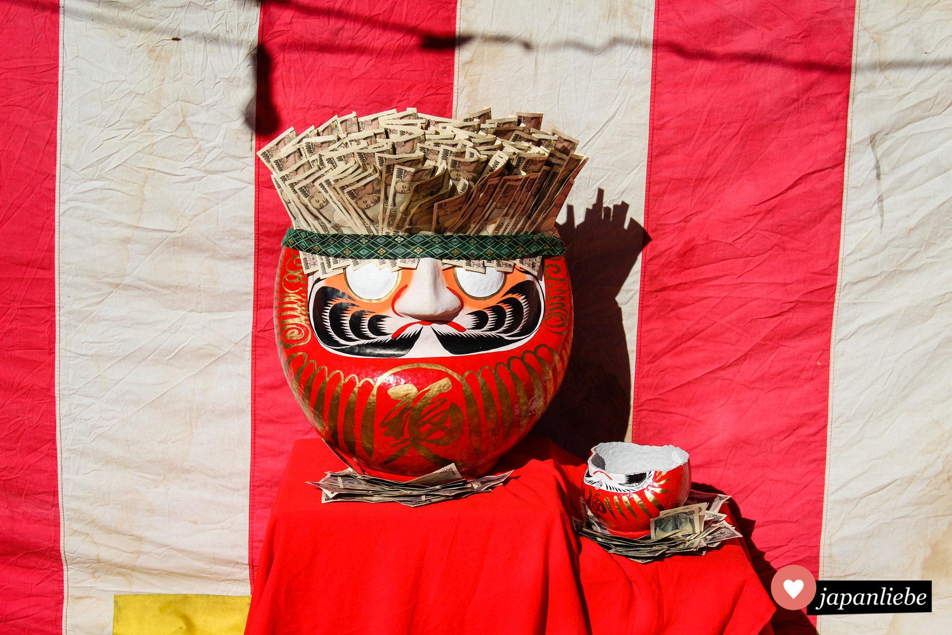Ein daruma am Kita-in Tempel in Kawagoe ist gefüllt mit Geldscheinen.