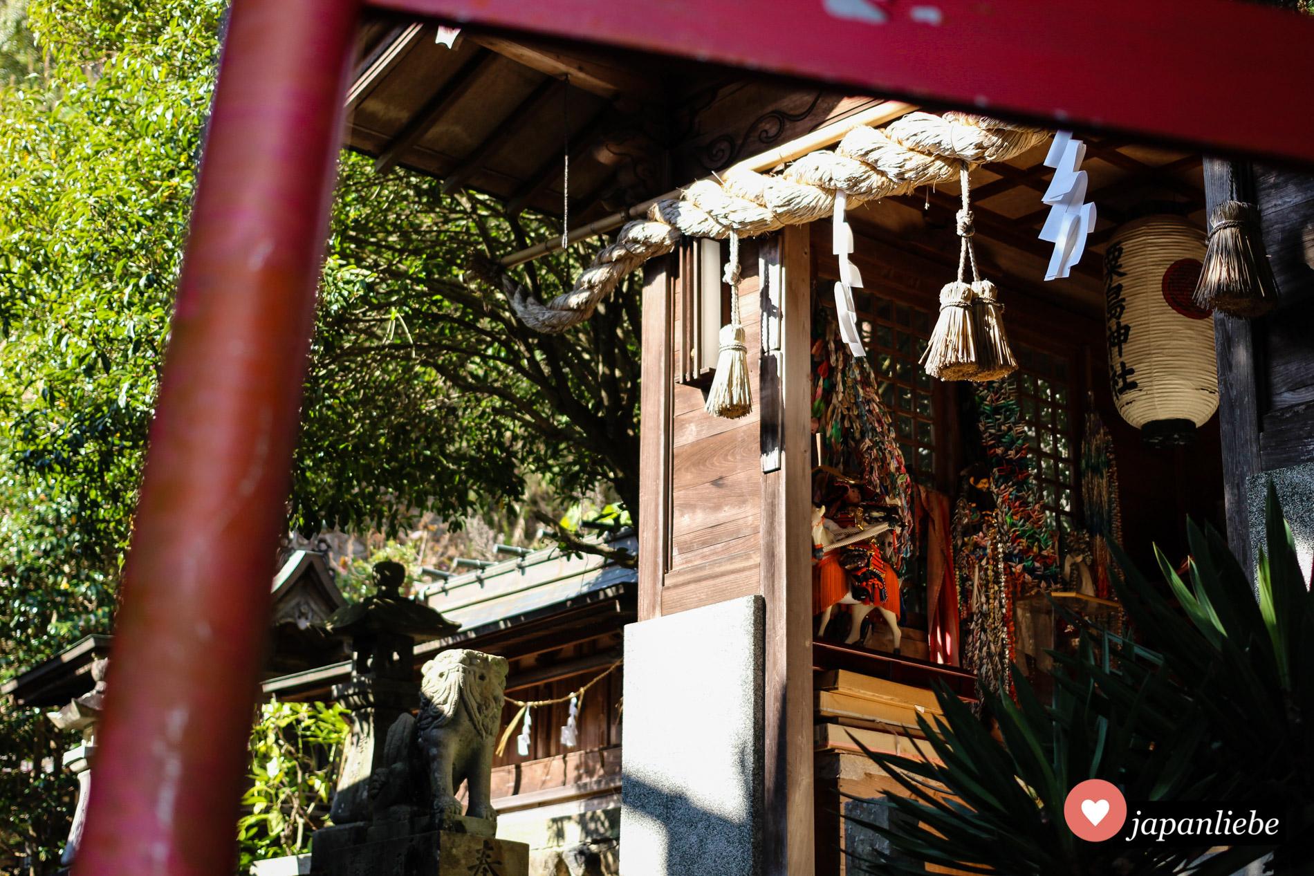 In einem Nebengebäude des Taga-Schreins hängen Origami-Kraniche auf Schnüren aufgefädelt und ausgediente Puppen und Plüschtiere.