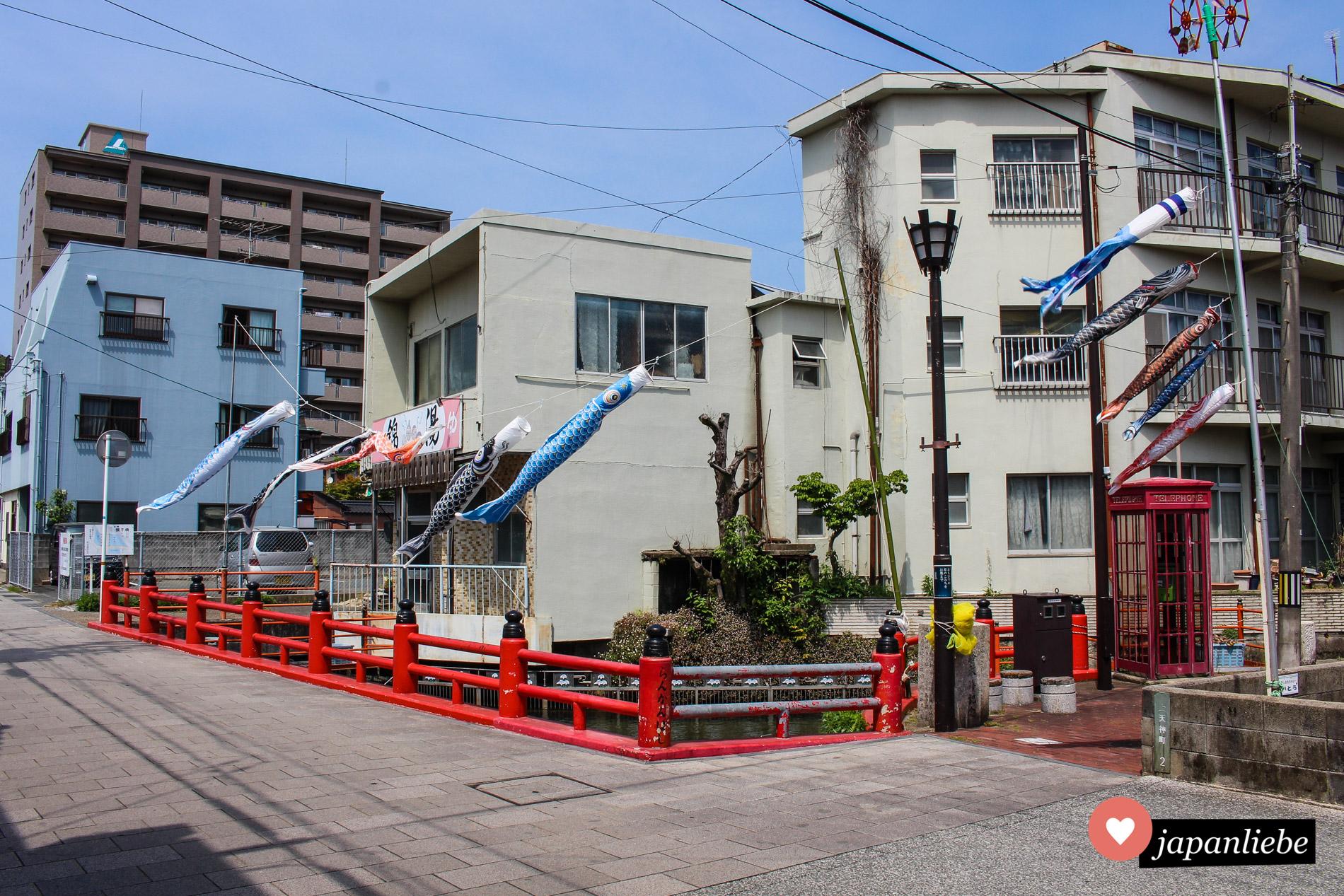 An einem kleinen Bach in der Innenstadt von Hōfu sind Karpfenfahnen zur Deko aufgehängt worden.