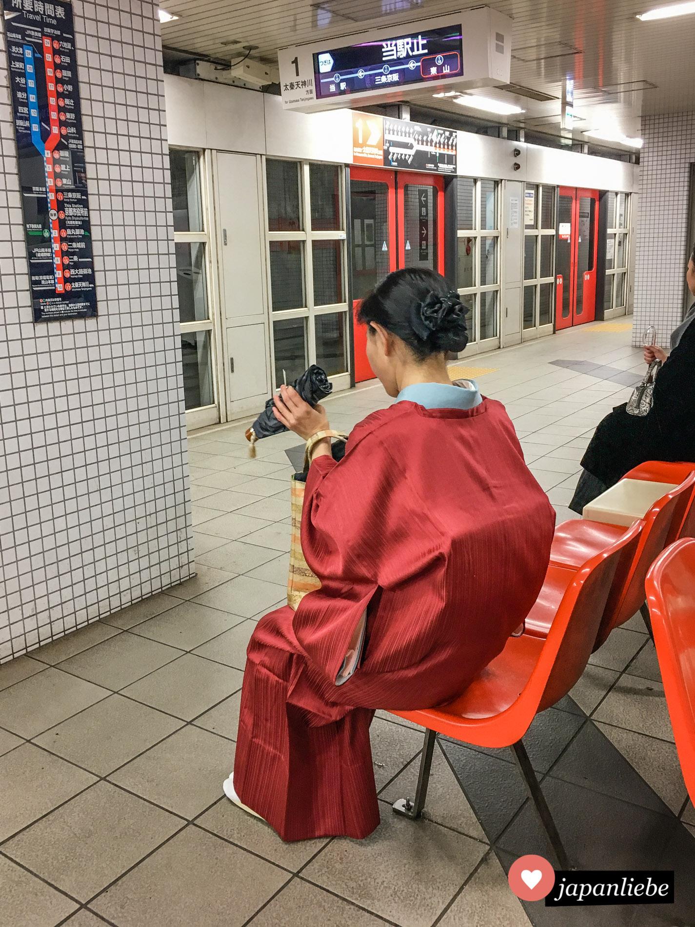 Eine Frau im Kimono wartet auf die U-Bahn.