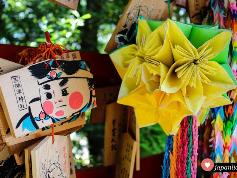 Eine ema-Wunschtafel am Kibistu-Schrein zeigt den Pfirsichjungen Momotarō.
