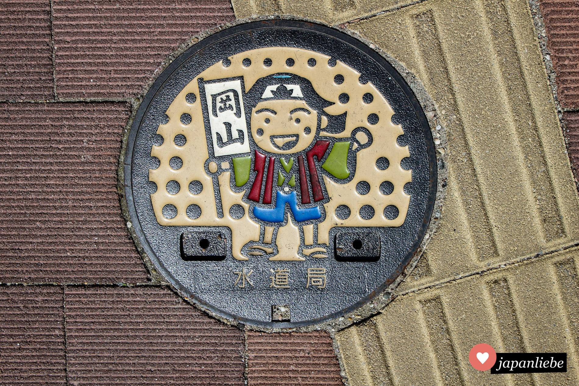 Ein bunter Kanaldeckel in Okayama zeigt einen fröhlichen Momotarō.