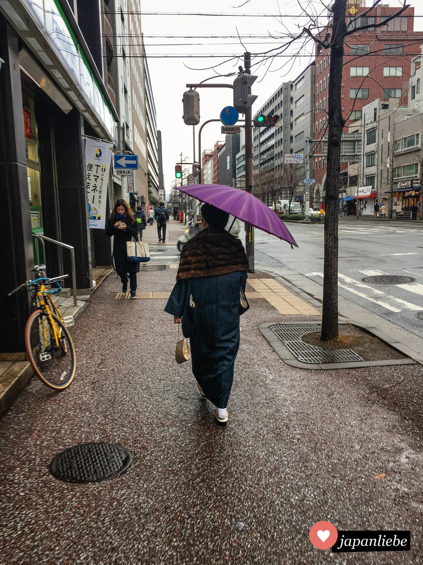 An einem regnerischen Tag in Kyōto ist eine Frau mit Kimono und Regenschirm unterwegs.