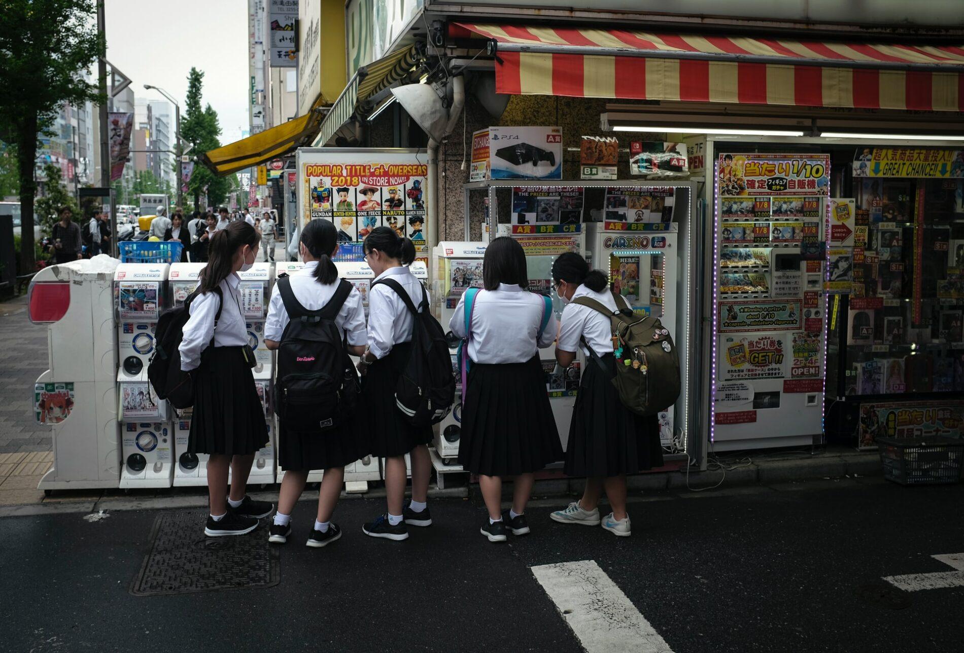 Junge Mädchen stehen nach der Schule an einigen Gashapon-Automaten in Akihabara. (Foto: Hakan Nural auf Unsplash https://unsplash.com/photos/8l8gQsG4c-E)