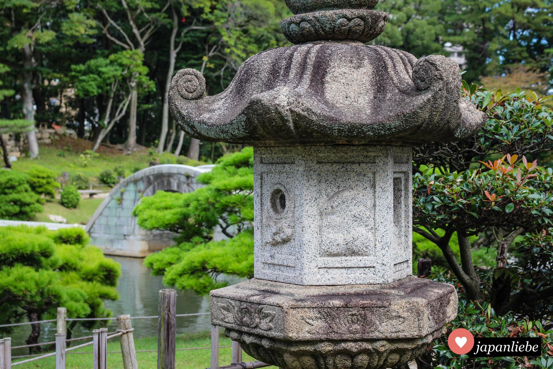 Eine Steinlaterne vor der Steinbrücke, die als einziges im Garten Shukkei-en die Detonation der Atombombe überstand.