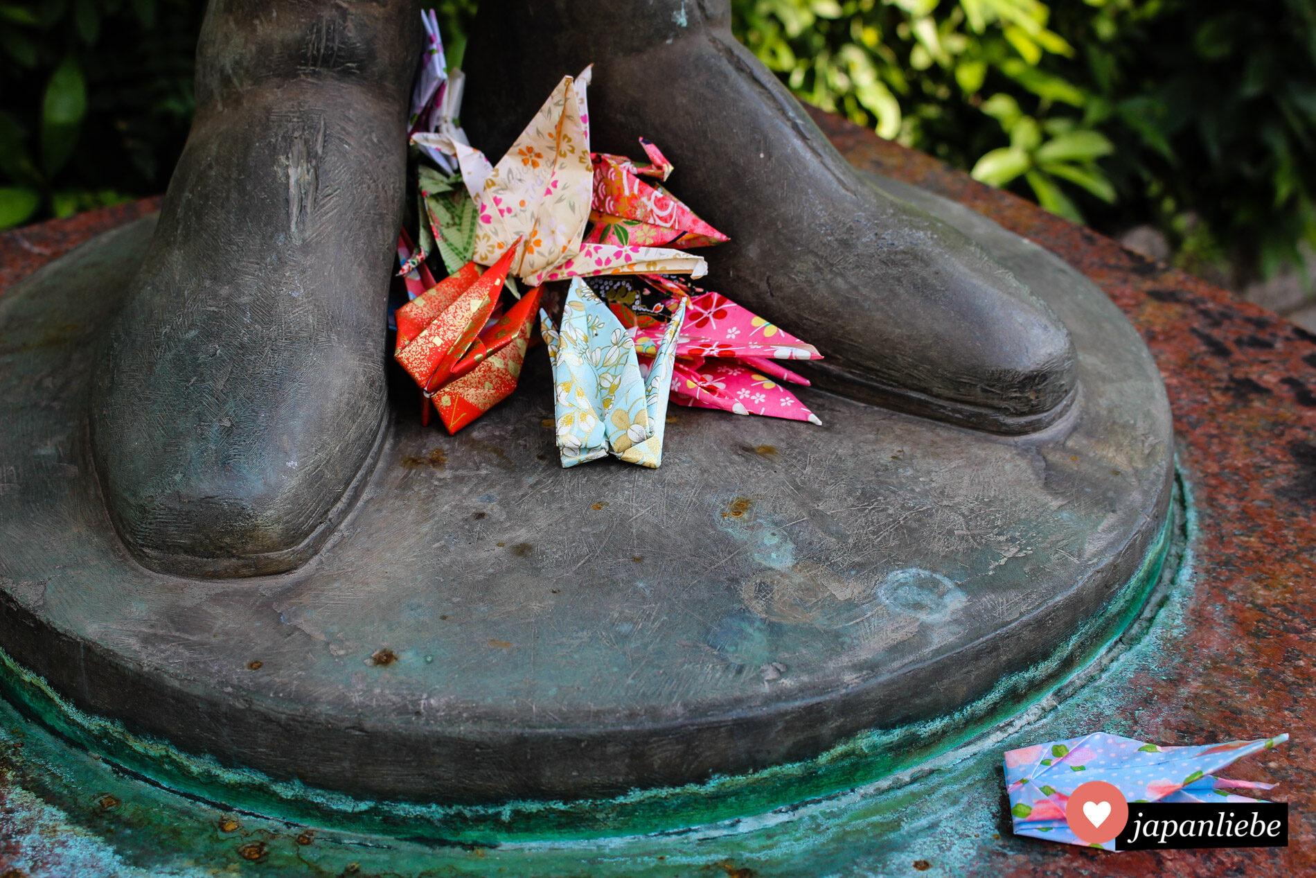 gefaltete Kraniche zu Füßen einer Sadako-Sasaki-Statue in Hiroshima.