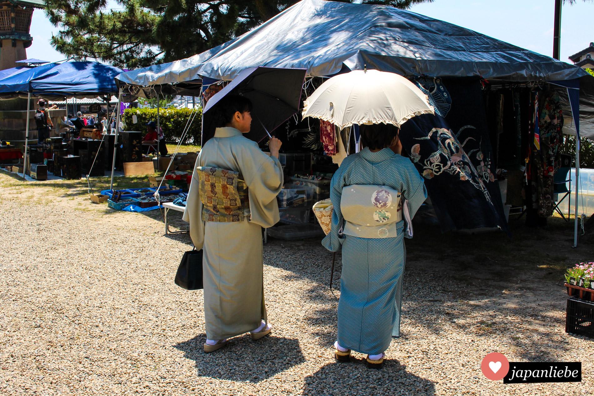 Zwei Japanerinnen schlendern in Kimonos über einen Flohmarkt am Izumo-taisha-Schrein.