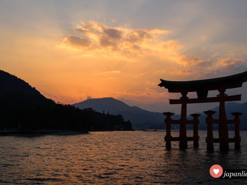 Das berühmte Schreintor des Itsukushima-Schreins auf der heiligen Insel Miyajima vor der Küste Hiroshimas bei Sonnenuntergang und Flut.