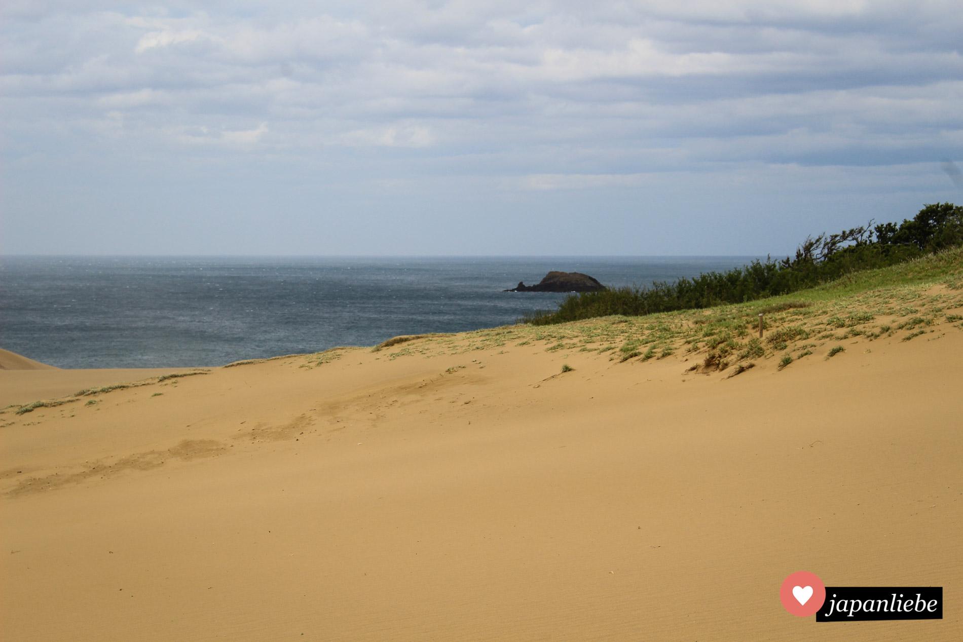 Die goldenen Sanddünen von Tottori heben sich gegen das Türkisblau des Japanischen Meeres ab.
